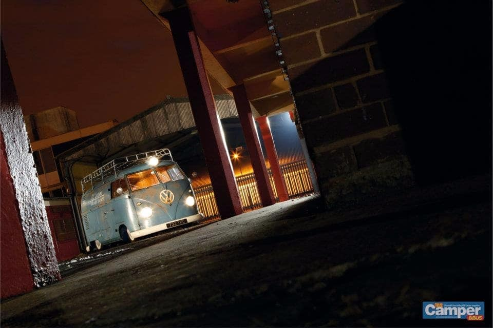 blue VW camper van at night with lights on in yard