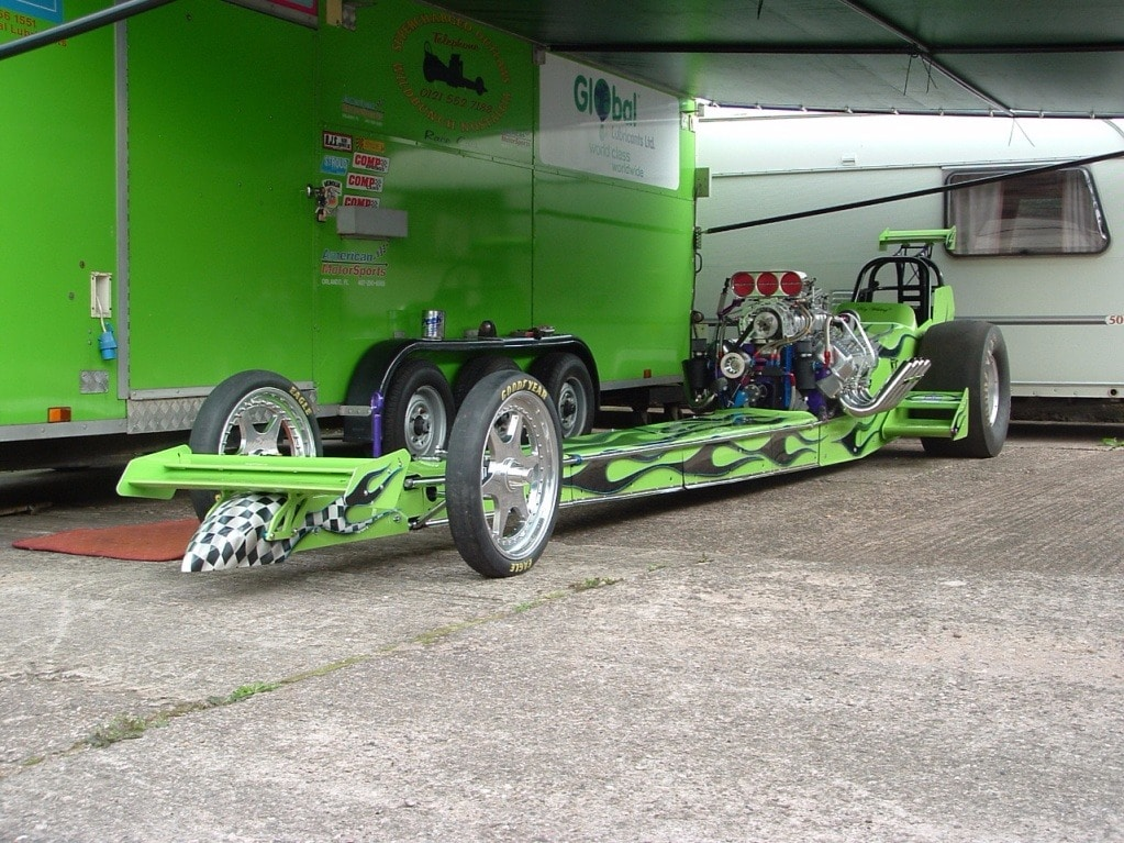 dragster parked next to green mobile
